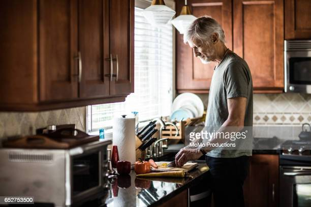 Portrait of man (60yrs) cooking at home