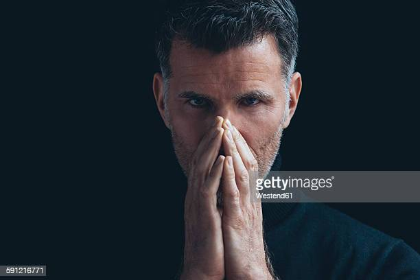 Portrait of man covering mouth with his hands in front of black background