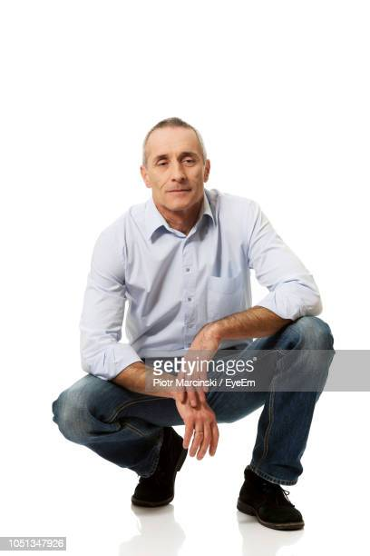 portrait of man crouching against white background - hurken stockfoto's en -beelden