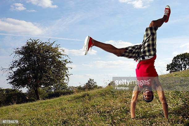 Portrait of man doing handstand in park