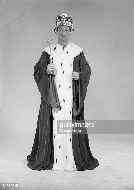 Portrait of man dressed as king against white backdrop