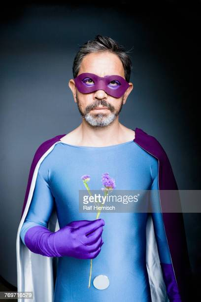 portrait of man dressed as superhero holding flower against gray background - purple glove stock pictures, royalty-free photos & images