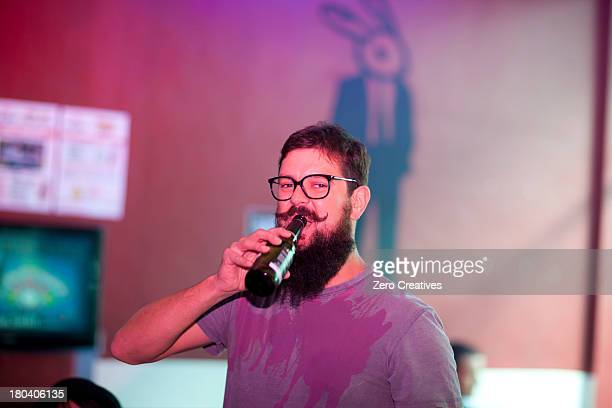 Portrait of man drinking bottle of beer in bar