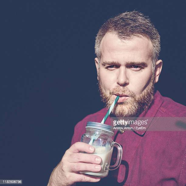 portrait of man drinking from mason jar against black background - mid adult men stock pictures, royalty-free photos & images