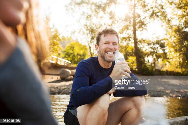 Portrait of man drinking water while sitting with woman on pier