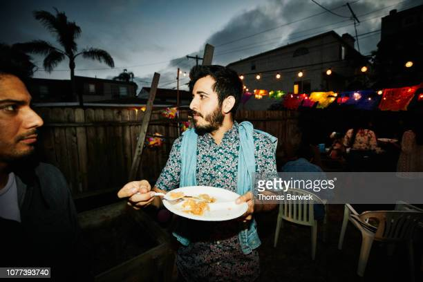 portrait of man eating during backyard barbecue on summer evening - only mid adult men stock pictures, royalty-free photos & images