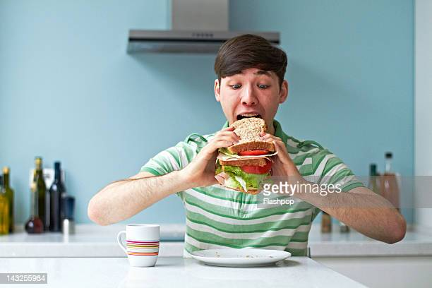 portrait of man eating giant sandwich - excess stock pictures, royalty-free photos & images