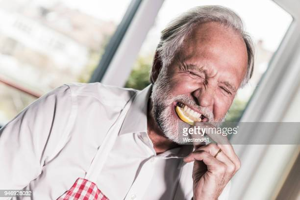 portrait of man eating lemon slice - sour taste stock pictures, royalty-free photos & images