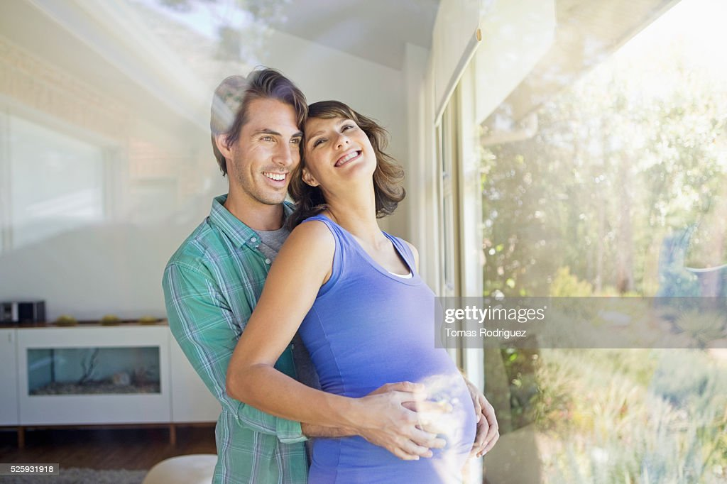 Portrait of man embracing pregnant woman : Bildbanksbilder