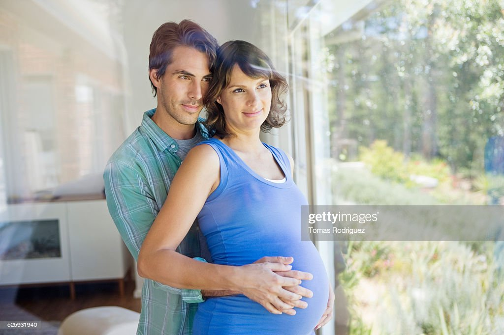 Portrait of man embracing pregnant woman : Photo