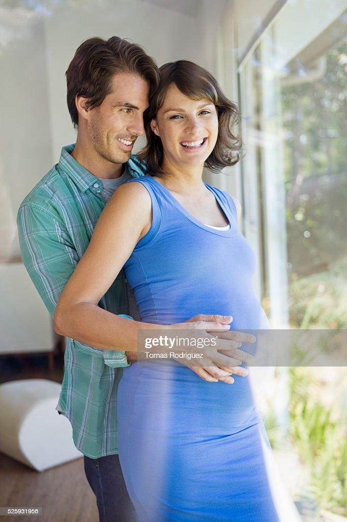 Portrait of man embracing pregnant woman : Stockfoto