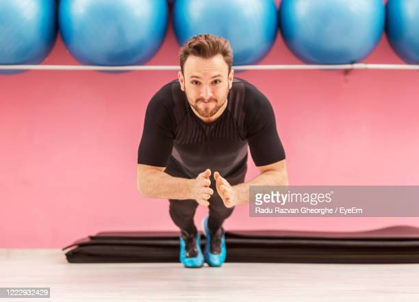 portrait of man exercising on floor in gym - one man only stock pictures, royalty-free photos & images