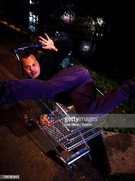 Portrait Of Man Falling In Shopping Cart At Night