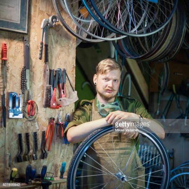 portrait of man fixing bicycle in small workshop - cadrage à la taille photos et images de collection