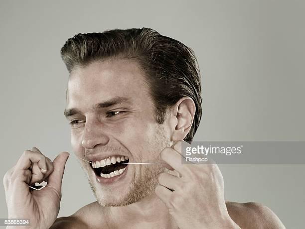 Portrait of man flossing his teeth