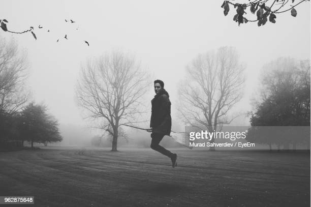 portrait of man flying on broomstick over field against sky - witch flying on broom stock photos and pictures