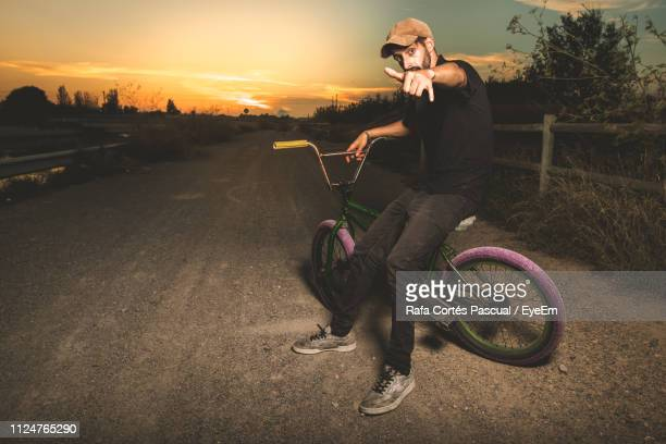 Portrait Of Man Gesturing Shaka Sign While Sitting On Bicycle Against Sky During Sunset
