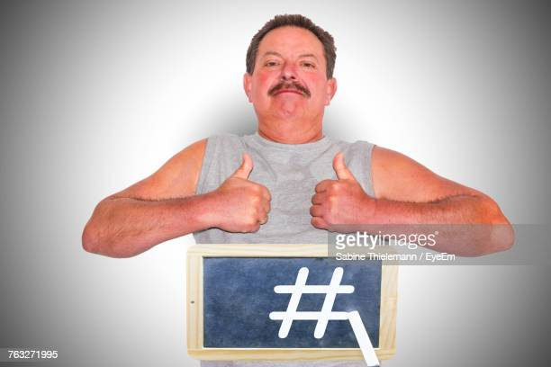 Portrait Of Man Gesturing Thumbs Up With Slate Against Gray Background