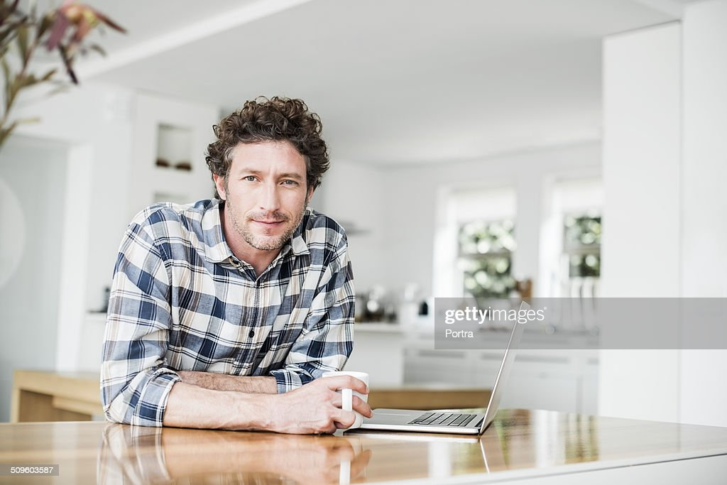 Portrait of man having coffee while using laptop : Stock Photo