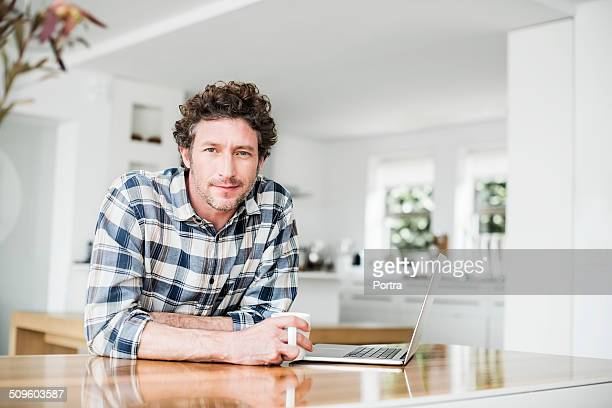 portrait of man having coffee while using laptop - 35 39 years stock pictures, royalty-free photos & images