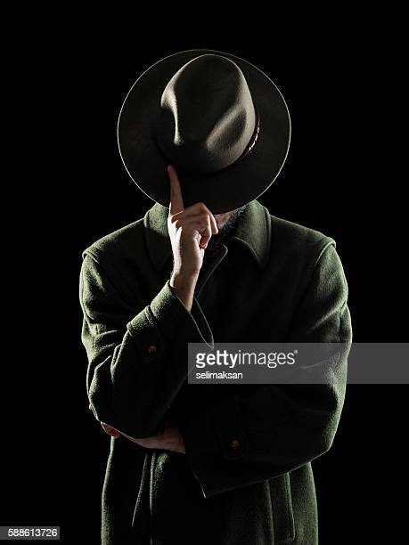 portrait of man hiding his face with fedora hat - mafia foto e immagini stock