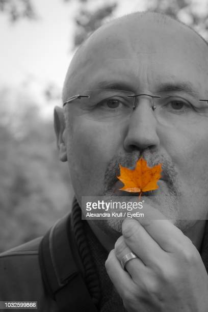 Portrait Of Man Holding Autumn Leaf