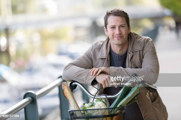 Portrait of man holding bicycle with vegetables in basket
