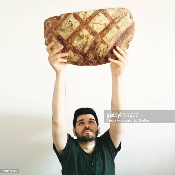 portrait of man holding bread against white background - matera stock photos and pictures