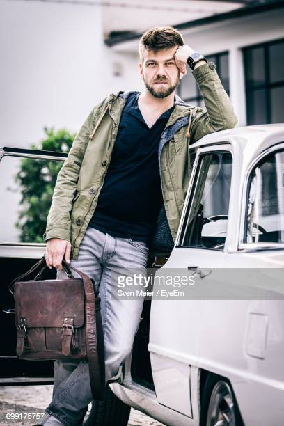 Portrait Of Man Holding Briefcase While Leaning On Car