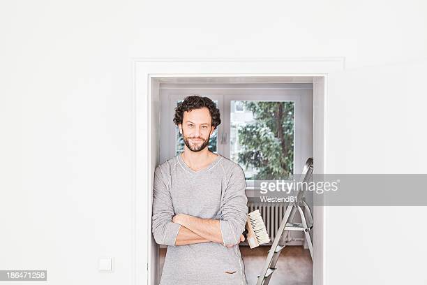 Portrait of man holding brush, smiling