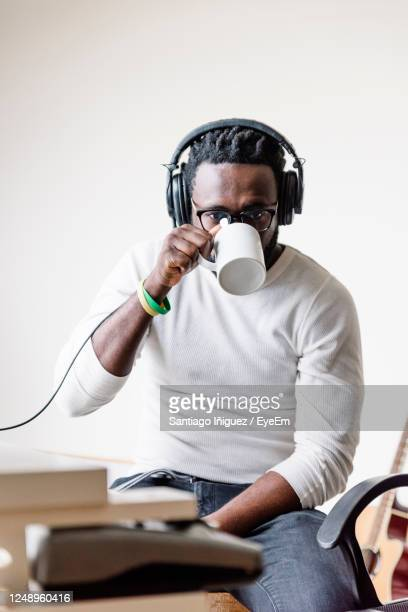 portrait of man holding camera while sitting on table - producer stock pictures, royalty-free photos & images