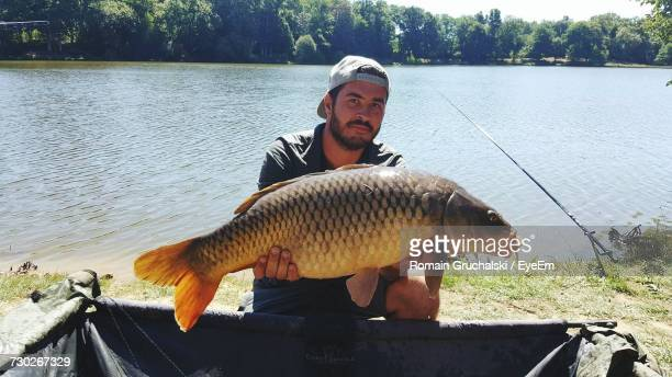 Portrait Of Man Holding Carp While Kneeling By Container At Lakeshore