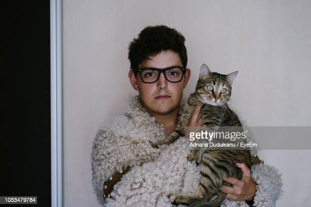 portrait of man holding cat against wall - winter coat stock pictures, royalty-free photos & images