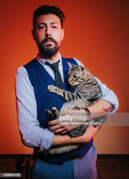 Portrait Of Man Holding Cat At Home