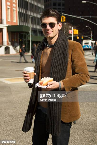 Portrait of man holding coffee and hot dog on city street