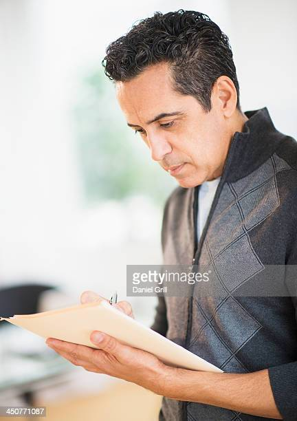 Portrait of man holding documents and writing
