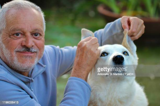 portrait of man holding dog ears - antonella di martino foto e immagini stock