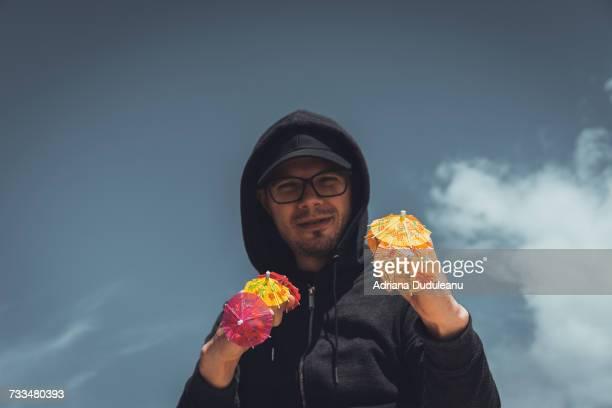 Portrait Of Man Holding Drink Umbrellas