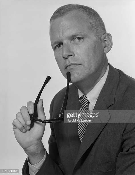 portrait of man holding eyeglasses - neckwear stock pictures, royalty-free photos & images