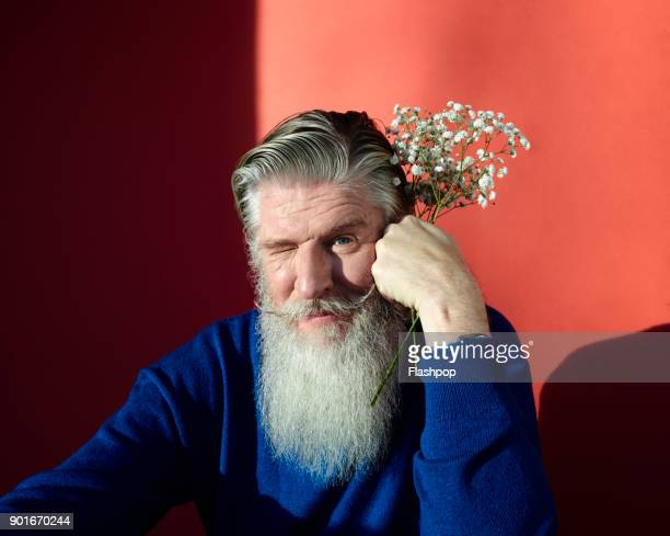 portrait of man holding flowers - offbeat stock pictures, royalty-free photos & images