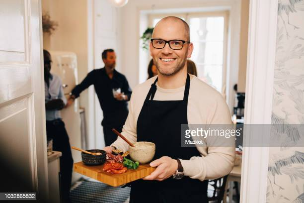 Portrait of man holding food in serving tray while standing at doorway