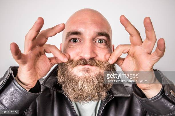portrait of man holding mustache against white background - completamente calvo foto e immagini stock