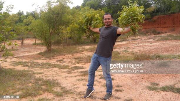 portrait of man holding neem leaves while standing against trees - neem tree stock pictures, royalty-free photos & images