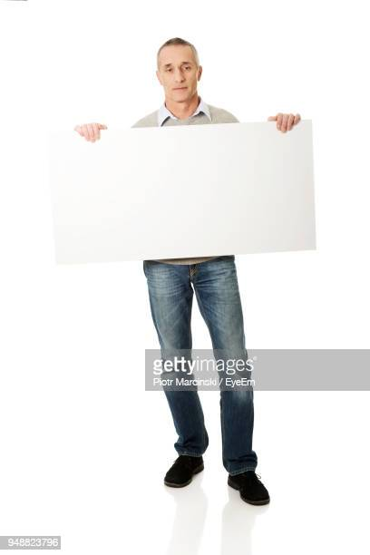 Portrait Of Man Holding Placard Against White Background