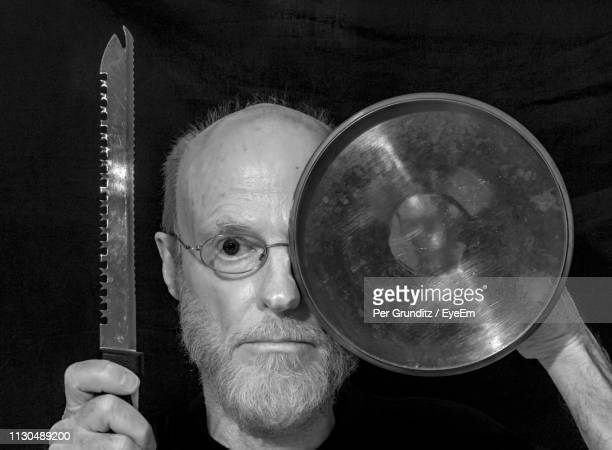 Portrait Of Man Holding Plate And Knife Over Black Background