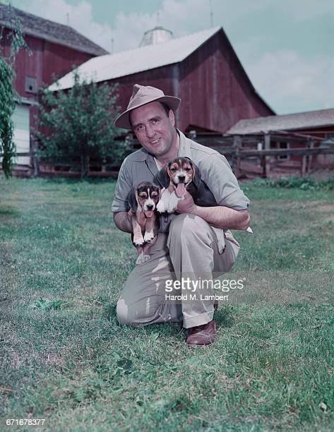 portrait of man holding puppy  - mamífero con garras fotografías e imágenes de stock