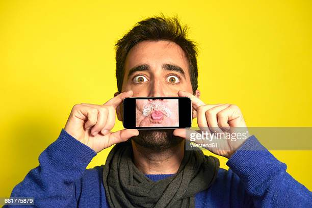 Portrait of man holding smartphone with photography of another mans pout