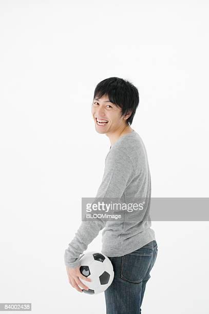 Portrait of man holding soccer ball, studio shot