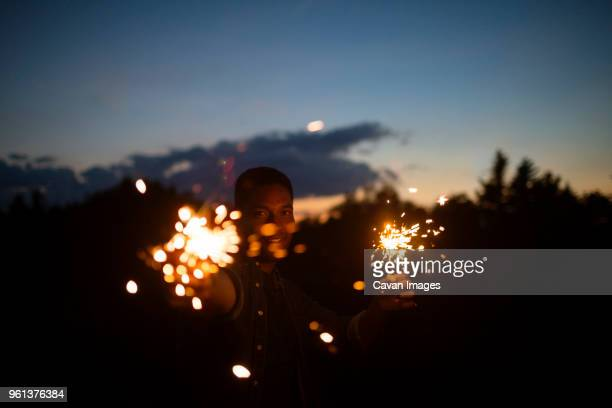 portrait of man holding sparklers against sky at night - one man only stock pictures, royalty-free photos & images