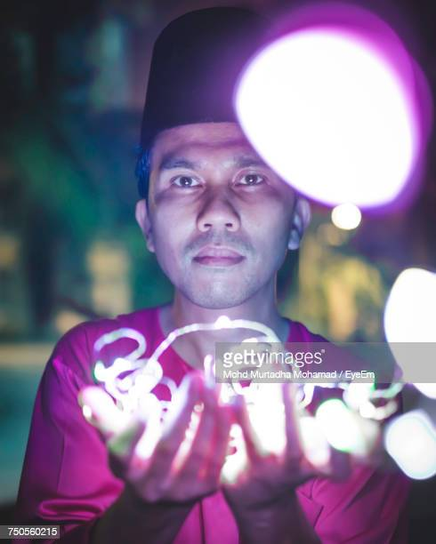 Portrait Of Man Holding String Lights At Night